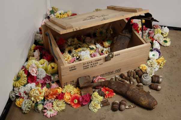 Flower-Shade, 2017, Wooden ammunition box, projectiles and ammunitions, articial owers, Size variable